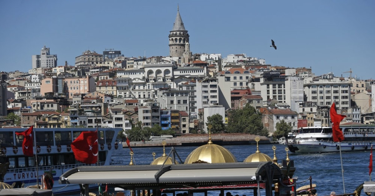 People walk near Istanbul's Golden Horn, with the iconic Galata Tower visible in the background, Aug. 14, 2018.
