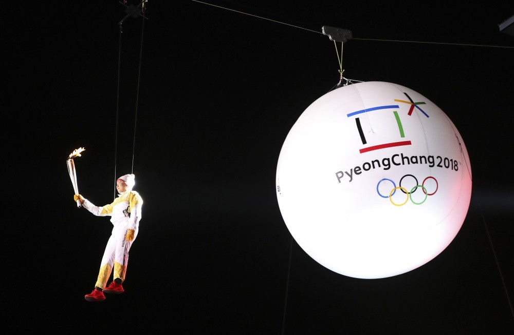 South Korean Ryu Seung-min, a member of the IOC Athletes Commission, carries the Olympic torch suspended from a wire during the Olympic Torch Relay in Incheon, South Korea.