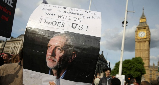 A protester holds up a placard in support of Leader of the opposition Labour Party Jeremy Corbyn outside parliament during a pro-Corbyn demonstration in central London on June 27, 2016. (AFP PHoto)