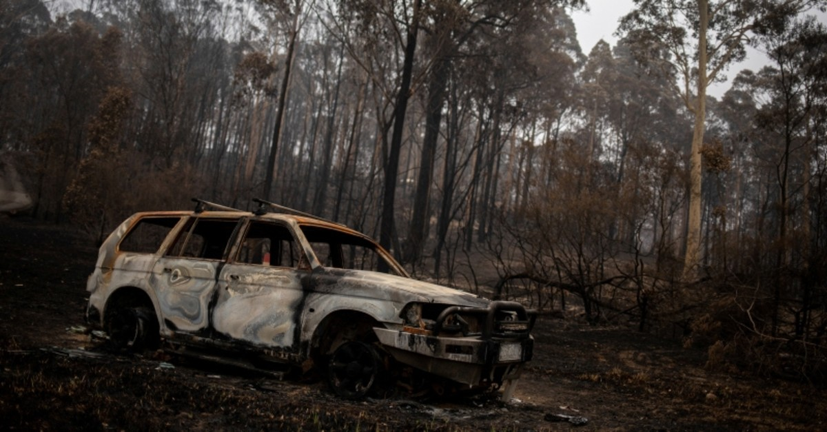 A destroyed car is seen next to burnt bushland in the village of Mogo, Australia January 8, 2020. (Reuters Photo)