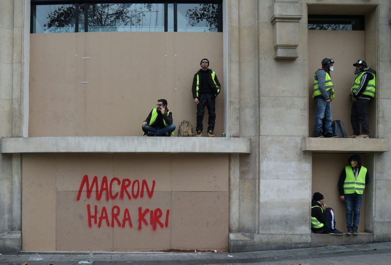 Protestors get some rest near an inscription reading ,Macron Hara Kiri, during a demonstration of yellow vests (gilets jaunes) against rising costs of living they blame on high taxes in Paris, on December 8, 2018. (AFP Photo)