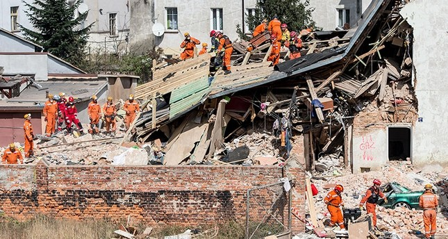 Polish emergency staff and firefighters work at the scene of a gas explosion that caused a tenement building to collapse in Swiebodzice, Poland. (EPA Photo)