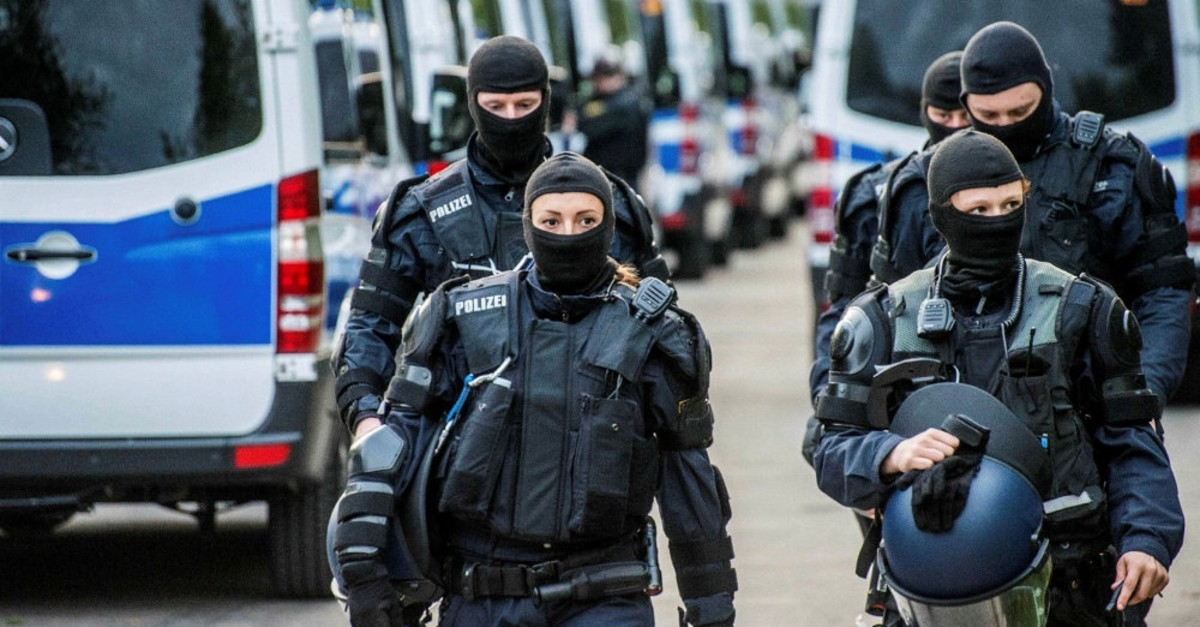 German police wear masks and body armor at a reception center for refugees, Ellwangen, May 3, 2018.