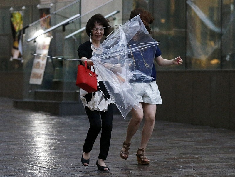 Women struggle with strong winds and rain caused by Typhoon Halong in Tokyo Aug. 10, 2014. (Reuters Photo)