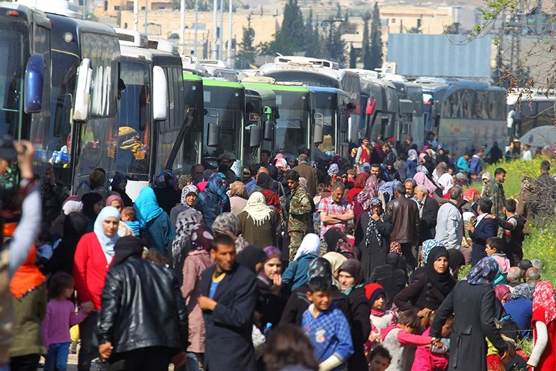 People that were evacuated from the two villages of Kefraya and al-Foua walk near buses, after a stall in an agreement between opposition and regime, at opposition-held al-Rashideen, Aleppo province, Syria, April 15, 2017. (Reuters Photo)