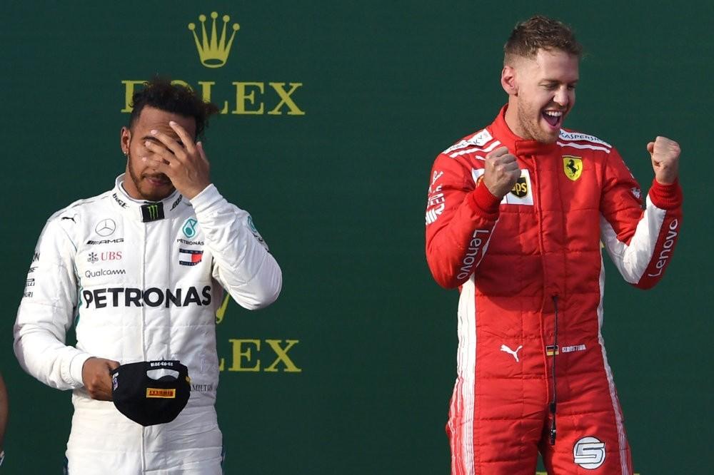 Ferrariu2019s Vettel celebrates his win on the podium with Mercedesu2019 Hamilton in the background on March 25.