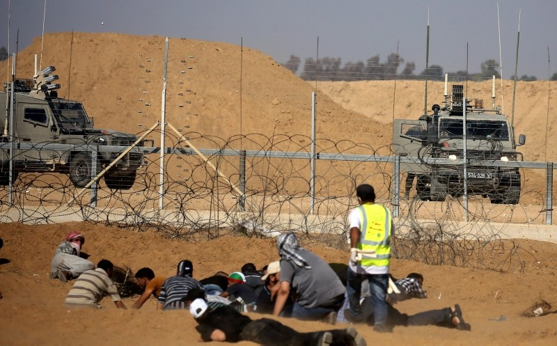Palestinian demonstrators take cover in front of Israeli troops during a protest demanding the right to return to their homeland at the Israel-Gaza border, in the southern Gaza Strip August 17, 2018. (Reuters Photo)