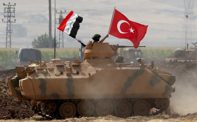 Soldiers hold Turkish (R) and Iraqi (L) national flags while standing in the turret of a Turkish armored vehicle during in a military exercise near the Turkish-Iraqi border in Silopi district, in Şırnak city, Sept. 26.