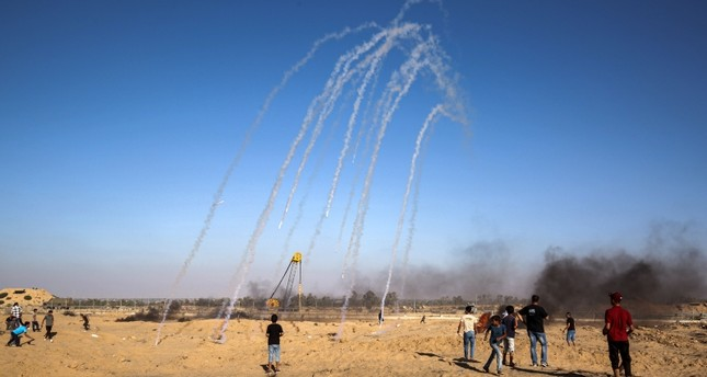 Tear gas canisters fired by Israeli forces across the fence fall amongst Palestinian protesters demonstrating along the border near Rafah in the southern Gaza Strip on July 19, 2019. (AFP Photo)