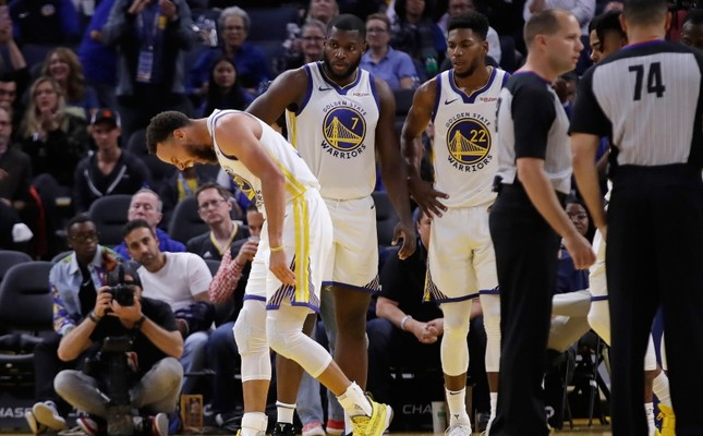 Golden State Warriors' Stephen Curry, left, grimaces after Phoenix Suns' Aron Baynes fell onto him during the second half of an NBA basketball game Wednesday, Oct. 30, 2019, in San Francisco. Curry left the game. (AP Photo)
