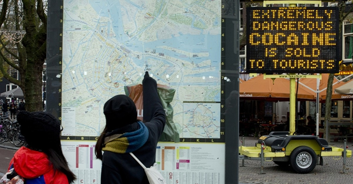 An electronic sign post warns tourists of extremely dangerous cocaine being sold to tourists on Rembrandtplein square in the center of Amsterdam, Netherlands, Thursday, Nov. 27, 2014. (AP Photo)