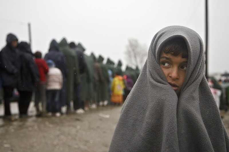 Migrant child covered in blanket stands in rain at the Greek border camp near Idomeni (AP File Photo)