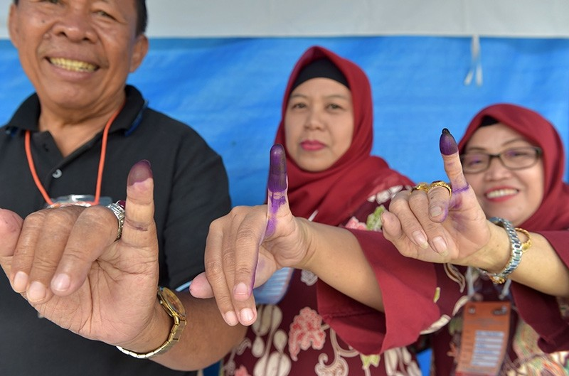 Indonesian people show their inked fingers after casting their ballots during regional elections in Tangerang, Banten on June 27, 2018. (AFP Photo)