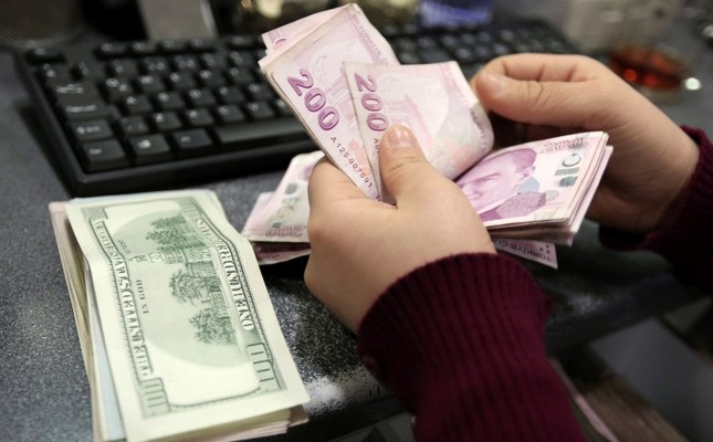 In this file photo taken Tuesday, Jan. 28, 2014, a woman counts U.S. dollar and Turkish lira banknotes at a currency exchange office in Istanbul, Turkey. (AP Photo)