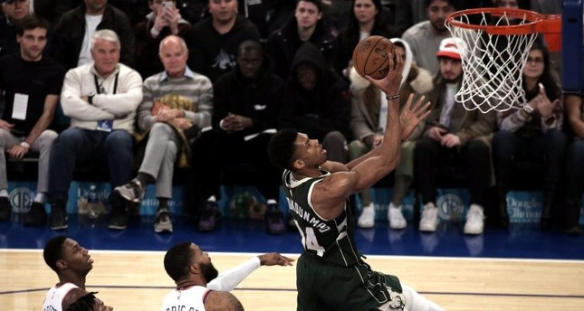 Bucks forward Giannis shoots over three Knicks defenders in the first half in New York, Dec. 21, 2019. EPA Photo