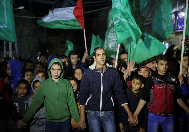 Supporters of Palestinian resistance group Hamas wave their green flags during a protest against the possible U.S. decision to recognize Jerusalem as Israel's capital, in Jebaliya Refugee Camp, Gaza Strip, Wednesday, Dec. 6, 2017. (AP Photo)