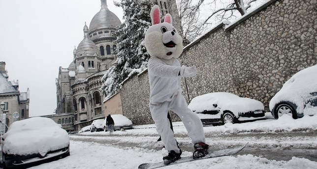 A man wearing a rabbit mask rides his snowboard down the Montmartre hill, with the Sacre Coeur Basilica in background, Wednesday, Feb.7, 2018 in Paris. (AP Photo)