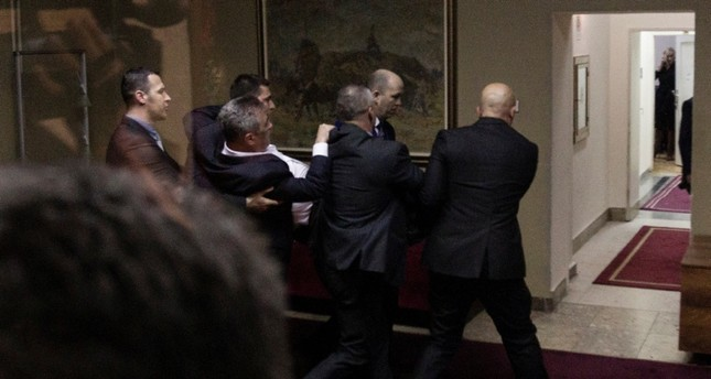 Police officers carry away opposition deputy Slaven Radunovic from the Democratic Front, after they tried to prevent the vote on a bill on religious freedoms & legal rights of religious organizations in Montenegro's parliament in Podgorica Reuters