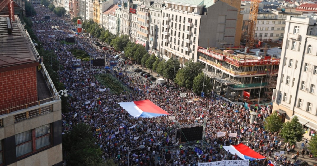 Protesters hold large Czech flags as they gather at the Venceslas Square in Prague, Czech Republic, Tuesday, June 4, 2019. (AP Photo)