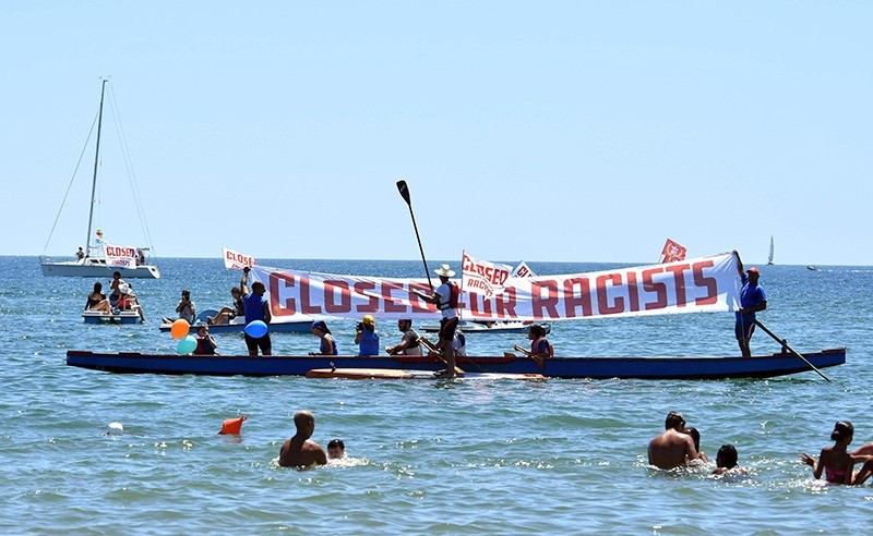 People hold banners and flags as they take protest against the scheduled arrival of the C-Star, a ship that an anti-immigrant group has chartered to try and halt migrant arrivals to Europe, in Catania, Sicily Island, Italy, July 29, 2017. (AP Photo)