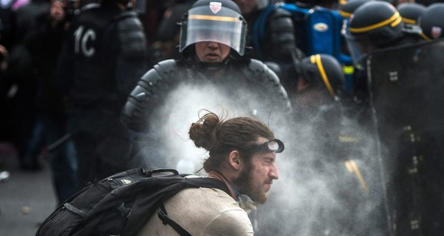 French police using tear gas against a demonstrator during a protest against the government's labor market reforms, at Place de la Nation, in Paris, May 26, 2016.