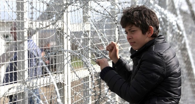 A boy looks through barbed wire as migrants wait to cross the Greek-Macedonian border near the village of Idomeni, March 1. (AFP Photo)