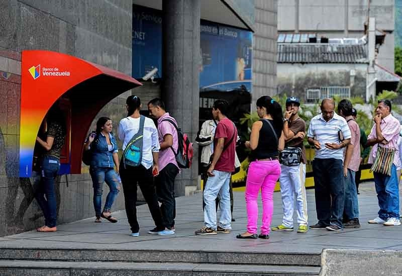 People queue to withdraw money from an ATM in Caracas on Nov. 14, 2017, as Venezuela declares selective default. (AFP Photo)
