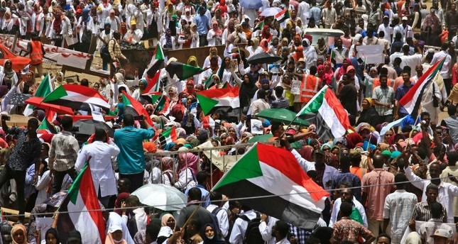 Sudanese protesters wave signs and flags as they continue to protest outside the army complex, Khartoum, April 17, 2019.