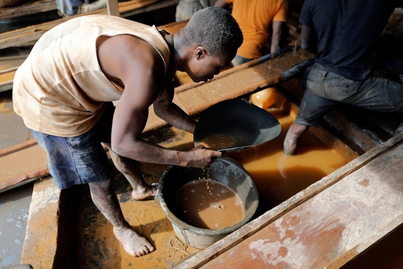 An artisanal miner pans for gold in alluvial sediment over a plastic bucket at the unlicensed mining site of Nsuaem Top in Ghana, November 23, 2018.