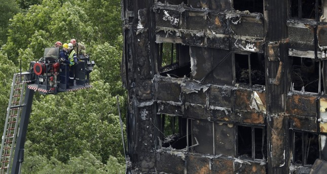 Emergency workers on a raised platform point at a section of the fire-gutted Grenfell Tower in London, Friday, June 16, 2017, after a fire engulfed the 24-story building Wednesday morning.