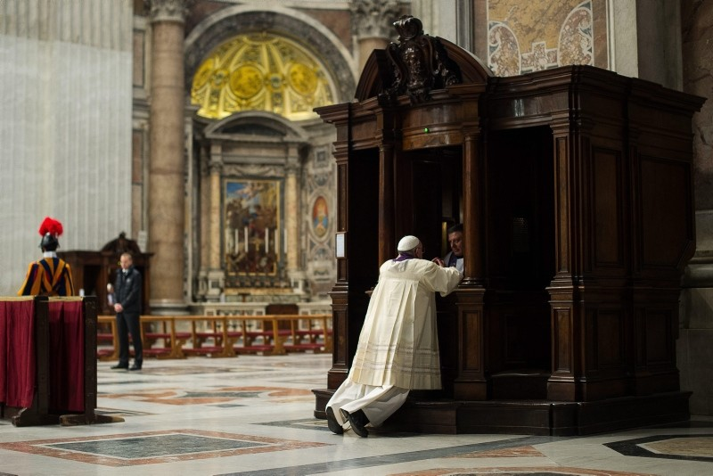 In this picture made available by the Vatican newspaper L' Osservatore Romano, Pope Francis is confessed by a priest in St. Peter's Basilica, at the Vatican, Friday, March 28, 2014. (AP Photo)