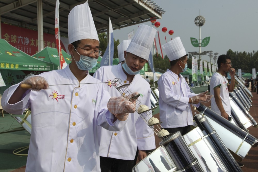 Chefs prepare buns in a solar cooker that uses a metal and glass vacuum tube heated by curved mirrors to capture the sunu2019s heat, in Dezhou in the eastern Shandong province, China.