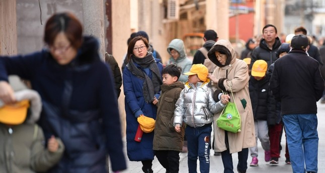 Parents and family members escort their children just outside the gates of an elementary school in Beijing following an attack on January 8, 2019 (AFP Photo)