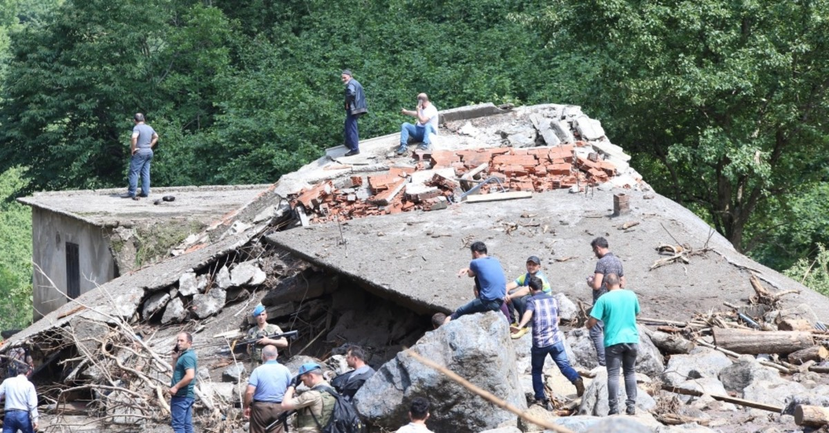 People stand around a building wrecked by rocks carried by flash floods in Araklu0131, Trabzon, June 19, 2019.