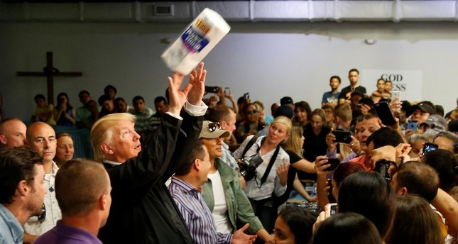 U.S. President Donald Trump tosses rolls of paper towels to people at a hurricane relief distribution center at Calvary Chapel in San Juan, Puerto Rico, October 3, 2017. (REUTERS)