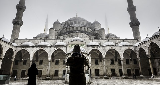 A young tourist snaps a photo of Istanbul's Blue Mosque on a foggy day (Sabah Photo File)