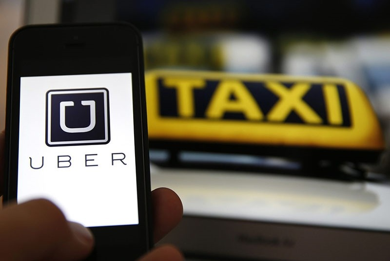 File illustration picture showing the logo of car-sharing service app Uber on a smartphone next to the picture of an official German taxi sign in Frankfurt, September 15, 2014. (Reuters Photo)