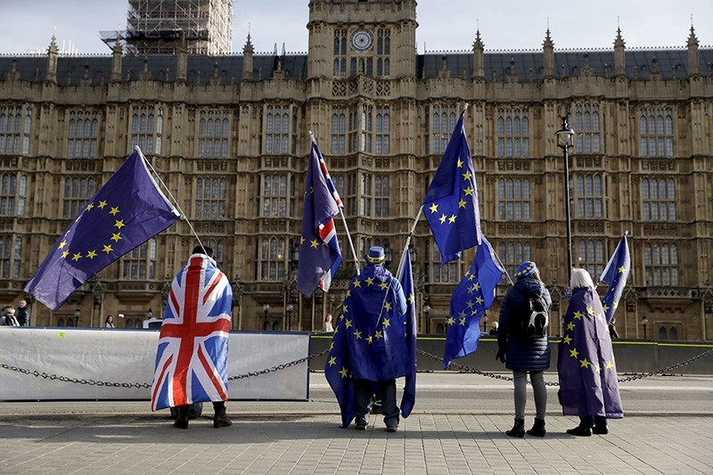 Pro-EU membership supporters hold European Union flags as they protest against Brexit across the street from the Houses of Parliament in London, Tuesday, Jan. 30, 2018. (AP Photo)
