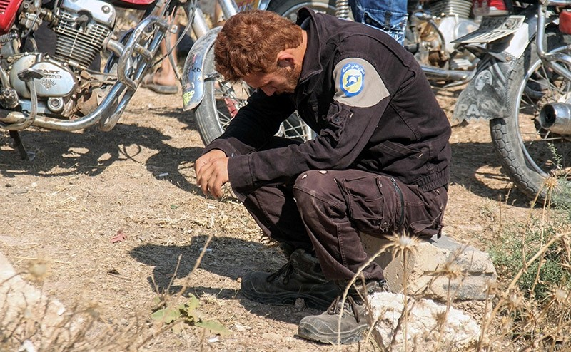 A member of the Syrian civil defence volunteers, also known as the White Helmets, mourns as colleagues bury his fellow comrades during a funeral in Sarmin (AFP Photo)