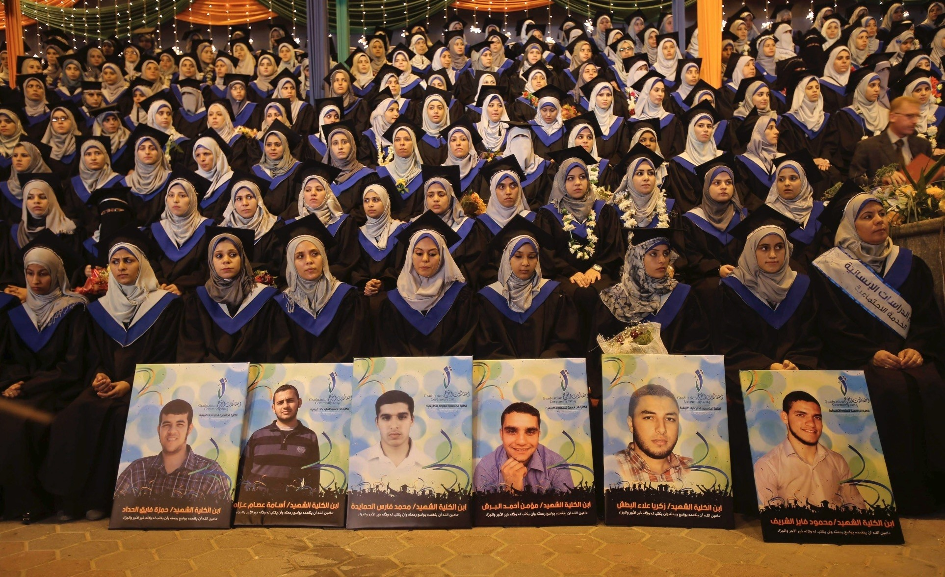 Palestinian graduates attend their graduation ceremony as they sit behind posters of the students who were killed by Israeli forces in a seven-week offensive, at the University College of Applied Sciences, Sept. 10, 2014.