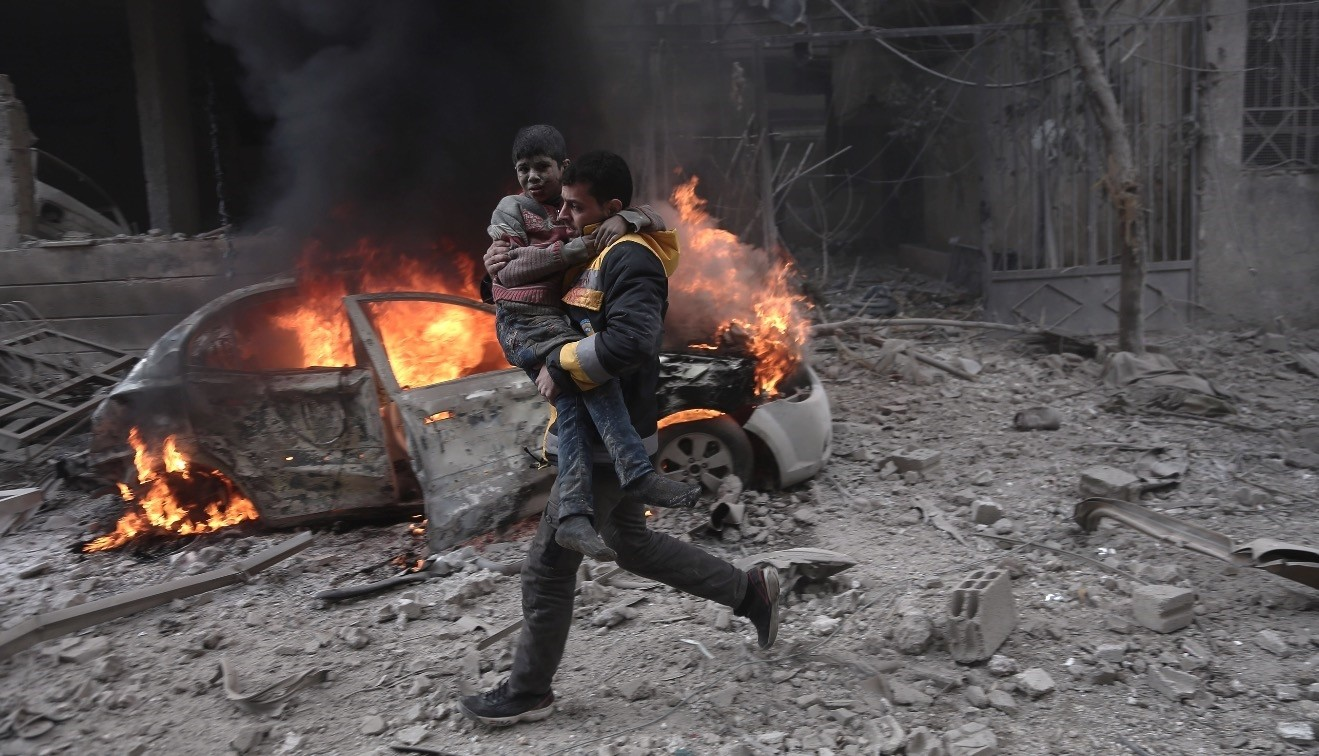 A Syrian paramedic carries an injured child following a reported bombardment by the Syrian regime in the opposition-held town of Hamouria, in Eastern Ghouta, Jan. 6.