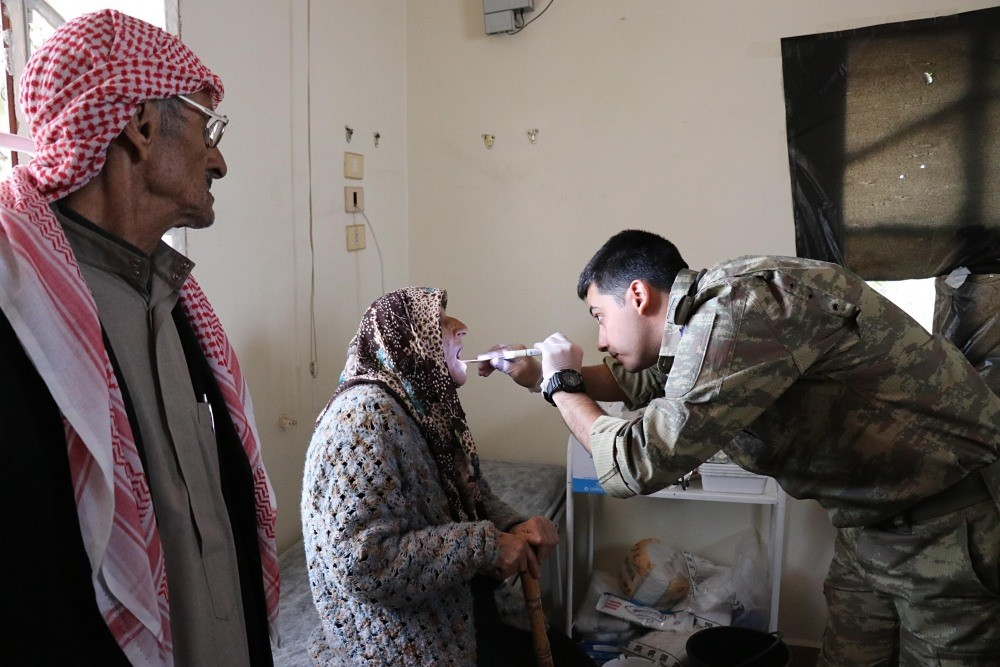 A Turkish officer treats an Afrin local at a medical clinic in rural Afrin.