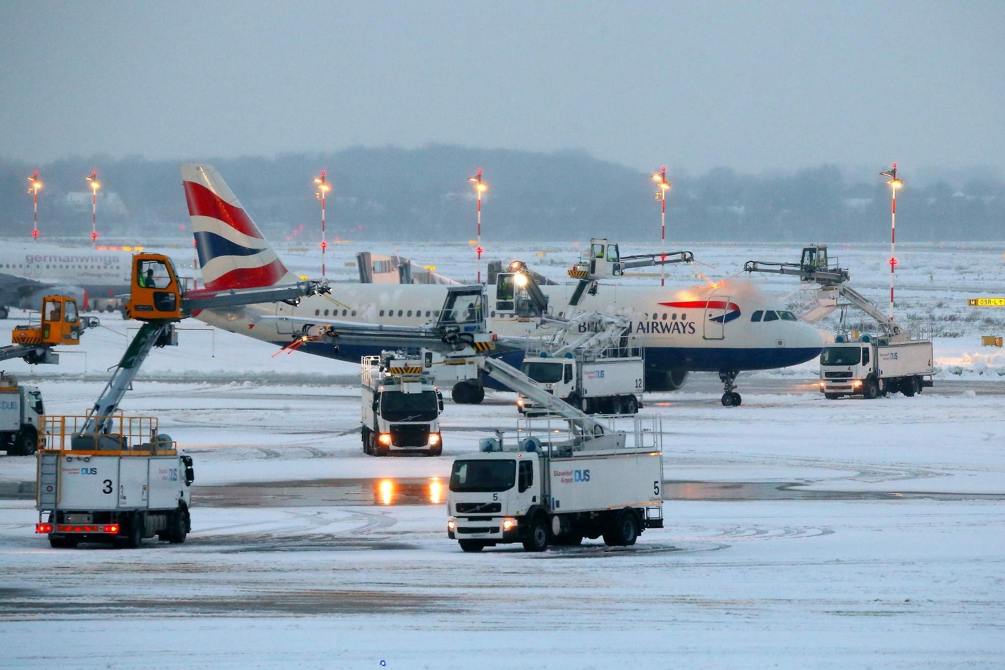 An airplane of British Airways is being de-iced as it stands on the tarmac of the airport in Duesseldorf, western Germany, on December 10, 2017. (AFP Photo)