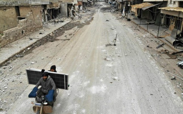 An aerial view shows Syrian men riding a motorcycle past destroyed shops in the village of Maaret al-Naasan in Idlib, Feb. 12, 2020. AFP