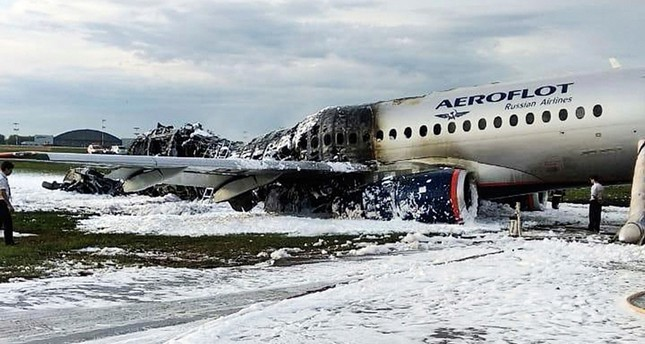 The Sukhoi Superjet 100 aircraft of Aeroflot Airlines is covered in fire retardant foam after an emergency landing in Sheremetyevo airport in Moscow, Russia, Sunday, May 5, 2019.  AP Photo