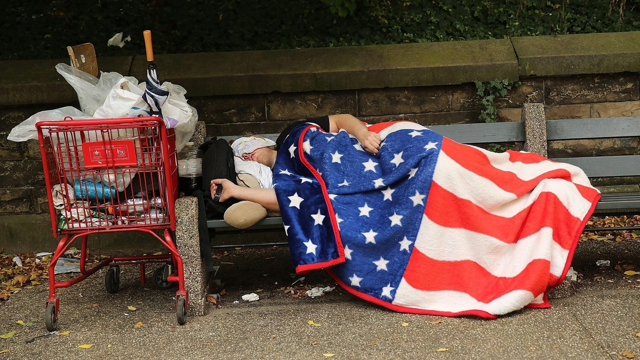 A homeless man sleeps under an American flag blanket on a park bench in New York City.