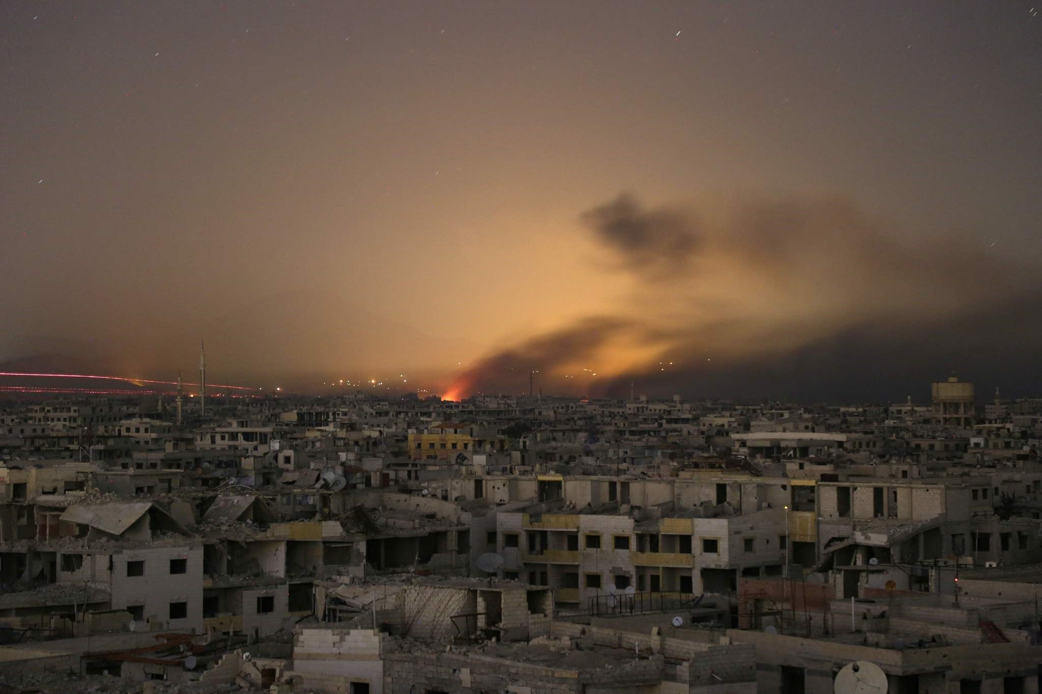 Lights and smoke are seen during regime bombardment on the rebel-controlled town of Arbin, in the besieged Eastern Ghouta region on the outskirts of the capital Damascus, on late March 11, 2018. (AFP Photo)
