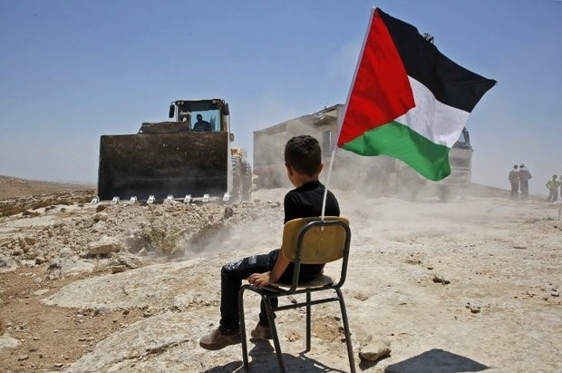 A Palestinian boy sits on a chair with a national flag as Israeli authorities demolish a school site in the village of Yatta, south of the West Bank city of Hebron, July 11.