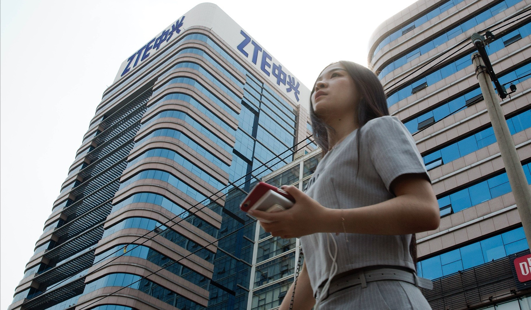 A woman pass by a ZTE building in Beijing, China, May 8.