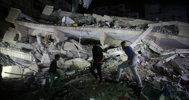 فلسطينيون بغزة يتفقدون مبنى تهدم بالكامل جراء القصف الإسرائيلي  (أسوشيتد برس)